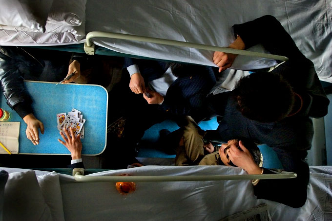 Businessmen play cards on a train originating in Shanghai and bound for the countryside of Anhui Province.