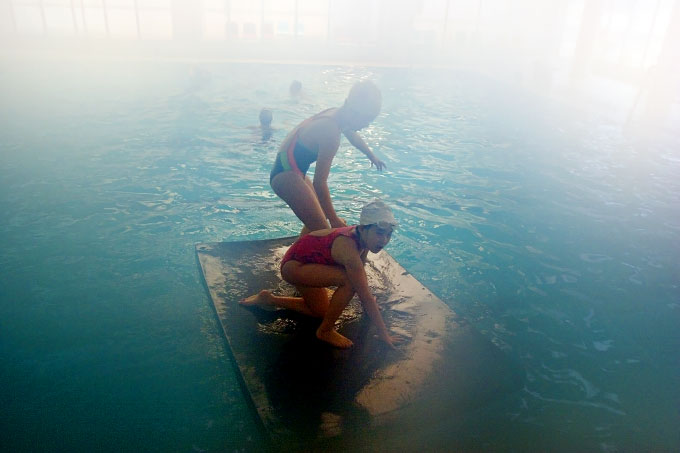 A heated indoor pool scene in Guangzhou, photographed through a foggy camera lens.