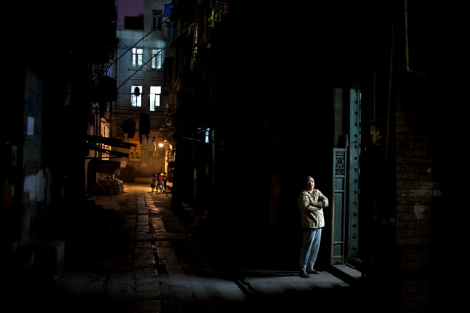 A woman waits for a shipment outside her home in the Old Canton neighborhood of Guangzhou.