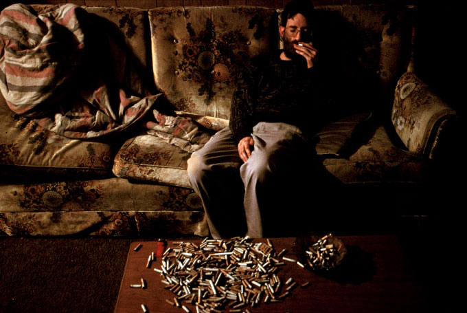 David Hartinger, a former mental patient at a mental institution in Athens, Ohio, sits on his couch. The cigarettes were collected from cigarette urns located outside local restaurants and grocery stores.