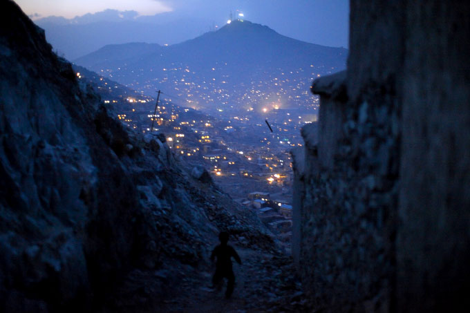 A child runs down a trail at dusk. Most of Kabul has only had 24-hour electricity since 2008.