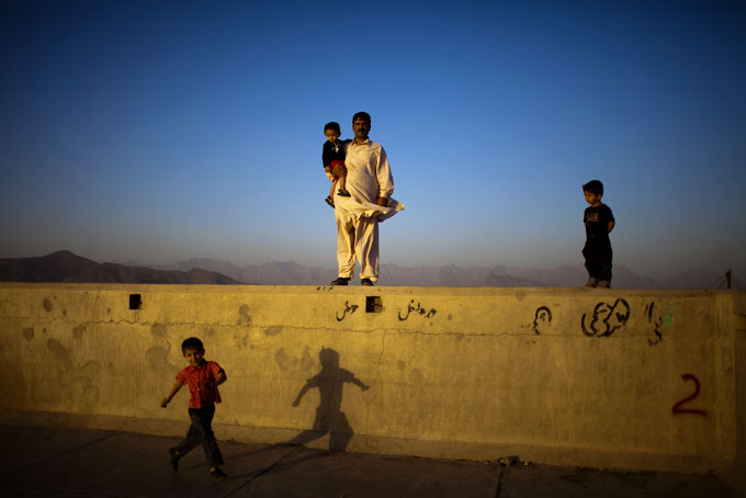 A family at an empty hilltop swimming pool in Kabul.