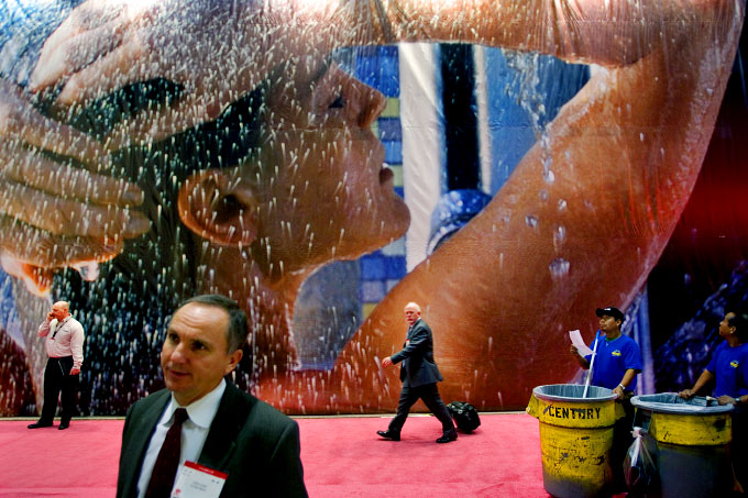 Workers and attendees walk by an advertisement for Kohler Faucets during the 2005 International Builders' Show, held at the Orlando County Convention Center.