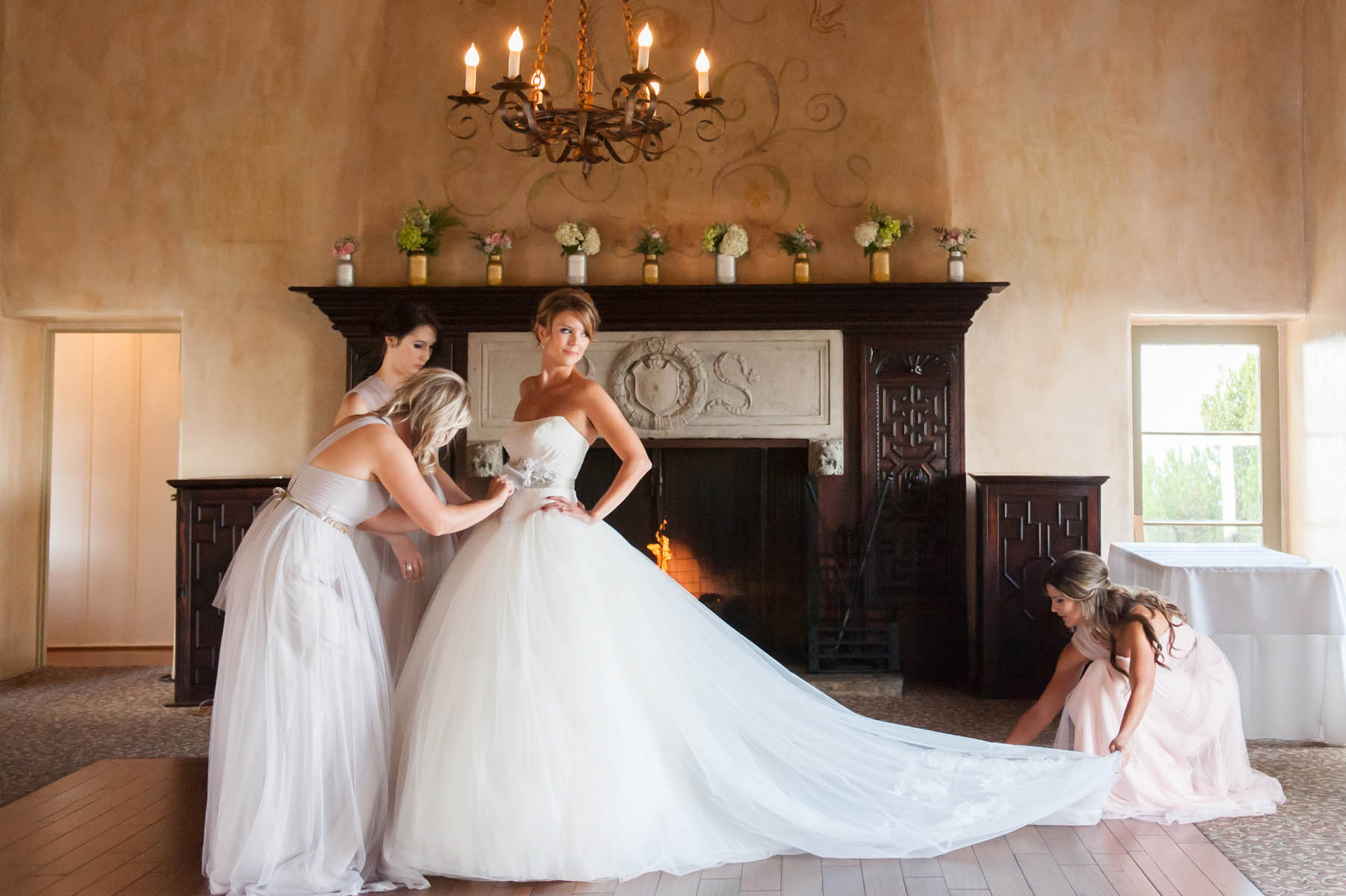 The bridesmaids help to smooth out the long train of the white wedding gown, as the bride looks over her shoulder. The room has a warm amber glow and there is a wood mantled fireplace in the background.