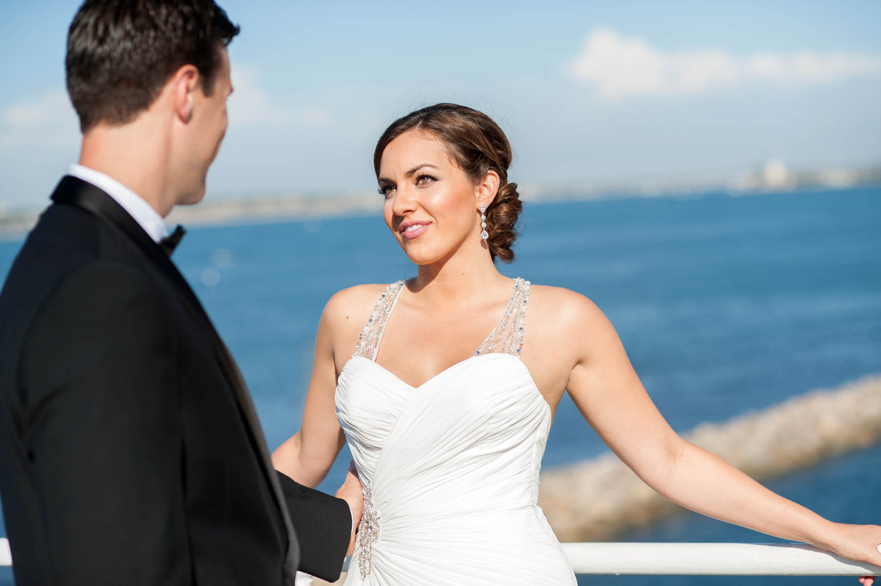 The bride leans against the railing of the ships deck and looks deeply into the eyes of her groom. The bright blue color of the sea and sky fill the background behind her.
