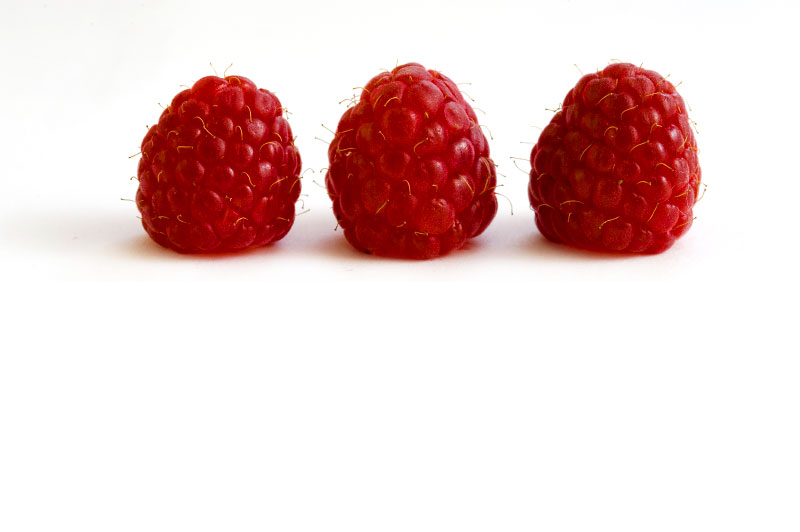 3 red raspberries on white background