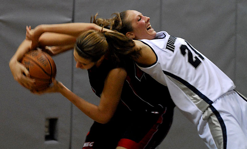 Monmouth's Jennifer Bender (right) bends backwards over St Francis' Janie Killian (left) in an attempt to regain control of the ball during the game at Monmouth University.