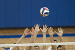 Volleyball players jump for the block during the game against Yeshiva University