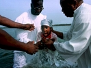 A child rises out of Broad Creek at Hilton Head Island as church elders baptize her. River baptisms are still a common tradition in the African-American church in the lowcountry region along the coast of South Carolina and Georgia.