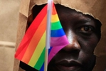 An asylum seeker from Uganda covers his face with a paper bag in order to protect his identity as he marches with the LGBT Asylum Support Task Force during the Gay Pride Parade in Boston, Massachusetts June 8, 2013. Homosexuality in Uganda is illegal and carries a potential penalty of life in prison.