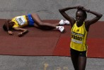 Second place finisher Dire Tune, of Ethiopia, (L) falls to the ground as Women's winner Salina Kosgei, of Kenya, walks away after crossing the finish line of the 113th running of the Boston Marathon in Boston, Massachusetts April 20, 2009.
