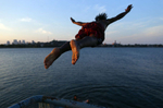 South Boston, Massachusetts -- 07/08/2014--   Edson Pontes, of Dorchester leaps off of a pier into Old Harbor in South Boston, Massachusetts July 8, 2014. Jessica Rinaldi/Globe StaffTopic: 09featureReporter: