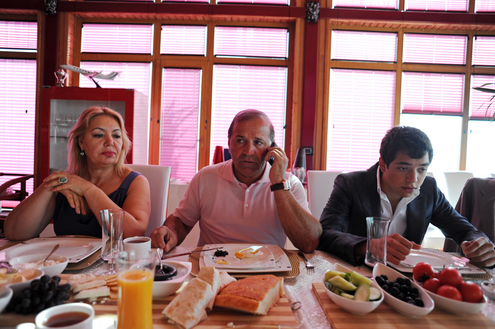GARADAGH BETWEEN SAHIL AND SANGACHAL, AZERBAIJAN.  (Center) Ibrahim Ibrahimov, an Azerbaijani oligarch and billionaire, talks on his cell phone at the breakfast table while seated between his wife (at left) Valida Ibrahimli and son Huseyn, 18, in one of several houses on his Caspian seaside property he used to inhabit with his family in the Garadagh region just southwest of Baku, Azerbaijan on July 18, 2012.  Ibrahimov is the developer behind the Khazar Islands artificial islands project; in his private life, he enjoys building a home for his family, moving in, and then quickly tires of the property before building a new home on an adjacent lot on his seaside lands.