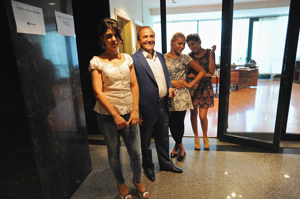BAKU, AZERBAIJAN.  Ibrahim Ibrahimov (second from left) with his girls, the secretaries in his office, in the hallway at Avesta Concern on Teymur Aliyev Street, known locally as the Oligarchs' Street, on August 16, 2012.