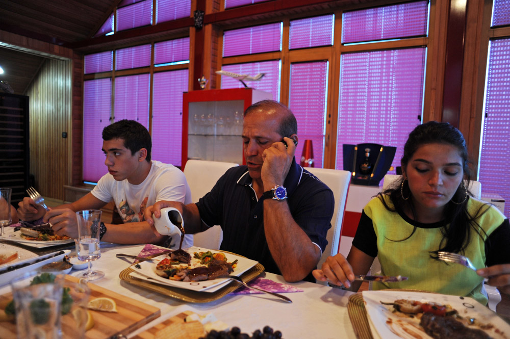 GARADAGH BETWEEN SAHIL AND SANGACHAL, AZERBAIJAN. Ibrahim Ibrahimov (center) talks on his cell phone as he sits at the dinner table and eats steak with his son Huseyn Ibrahimov, 18, and daughter Ilkana Ibrahimova, 22, in his home on August 16, 2012.