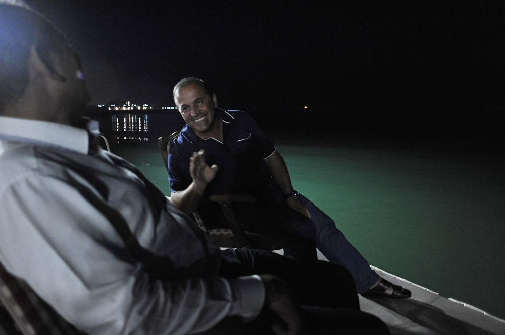 GARADAGH BETWEEN SAHIL AND SANGACHAL, AZERBAIJAN. Ibrahim Ibrahimov sits down after dinner by the Caspian Sea with a Turkish business associate, M. Tayfur Ozturk at the edge of his home on August 16, 2012.