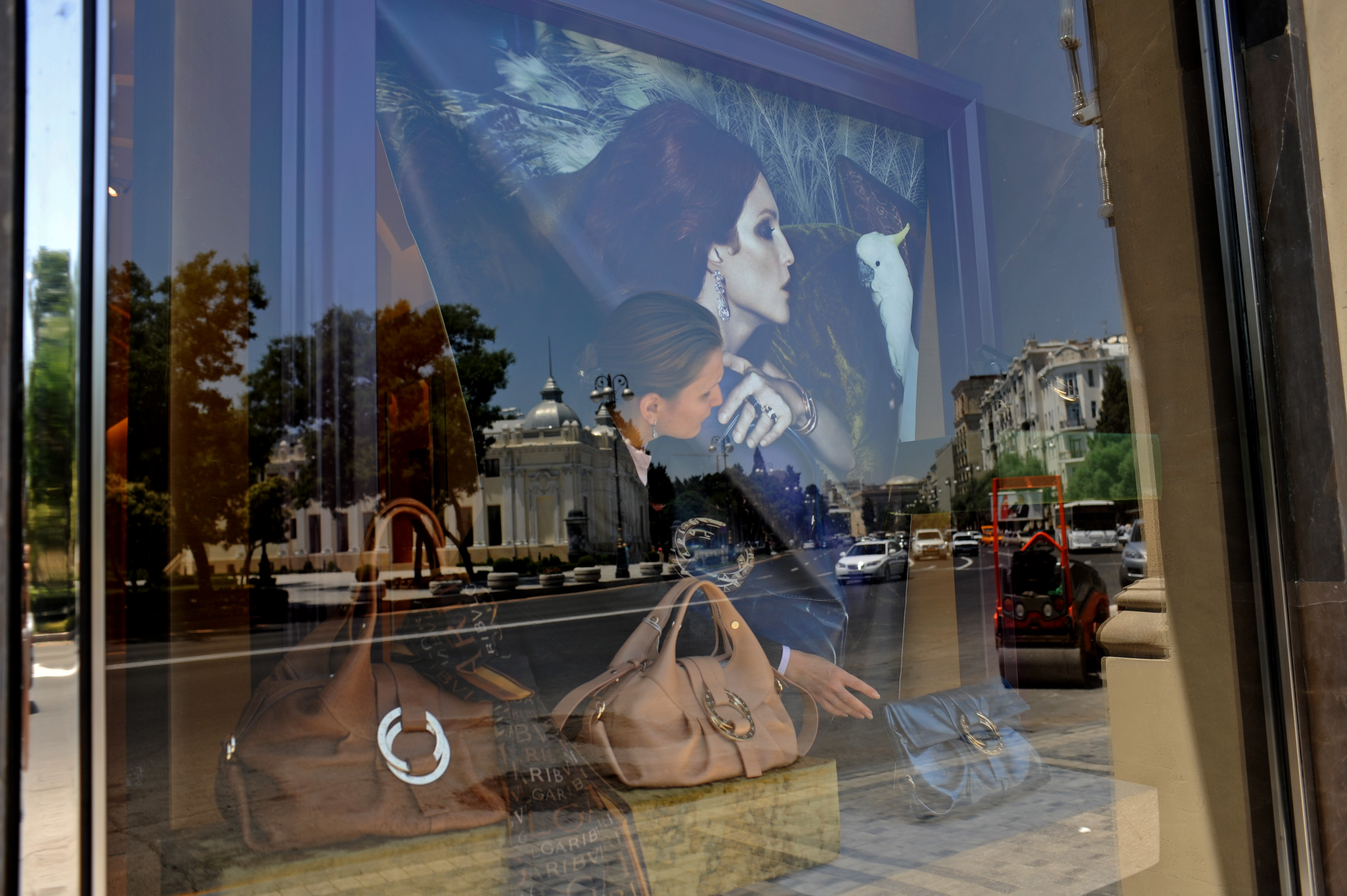 BAKU, AZERBAIJAN.  A saleswoman adjusts the window display at Bulgari on Neftiler Prospekt, or Oil Worker's Boulevard on July 2, 2010.  Luxury shopping in downtown Baku is one symptom of the city within the city or the country within the country where the elite, estimated at 50,000, control much of the country's income and profit from oil revenues, leaving a wide gap in the absence of a middle class between them and the rest of the country.