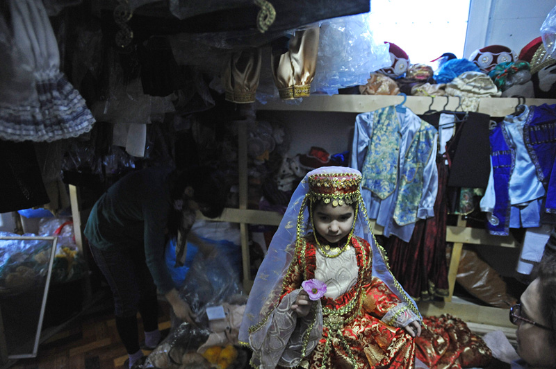 BAKU, AZERBAIJAN.  Rena Ibrahimova (center), 5, tries on a traditional Azeri costume in the attic of a woman, Farida, who started her own business making and manufacturing costumes for schoolchildren in school plays and productions on March 10, 2012.