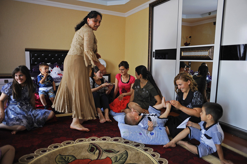 GIVRAKH, NAKHCHIVAN AUTONOMOUS REGION, AZERBAIJAN.  A day after the wedding and bride Khanim Veliyeva, 20, has joined her groom's family, her female relatives arrive for lunch, bring her her belongings and socialize with her in her new room in her groom's family's house on July 16, 2012.   After the bride is delivered to the groom's family's house, she will stay with the family and live the rest of her life in her new home.