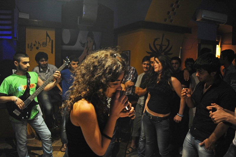 BAKU, AZERBAIJAN.  A young woman dances as a female singer and her band sings covers of American pop and classic rock songs during a youth party benefit for Free Youth, a youth organization, at the Amnesia Pub on June 28, 2012.