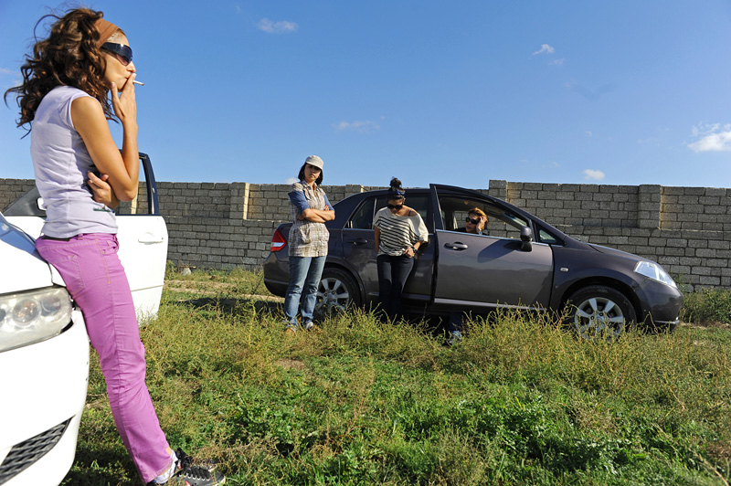 MASTAGAH, AZERBAIJAN.  (L-r) Animal rights activists hang out in and around their cars while waiting for materials to be prepared to build additional kennels for stray dogs they have rescued from the streets in a field on October 8, 2011.