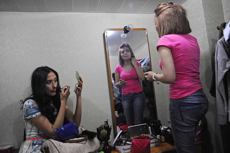 "BAKU, AZERBAIJAN.  Actresses apply more make up backstage between takes on the set of ""Javanliq,"" a show mirrored on ""Friends,"" in a small, makeshift television studio on May 1, 2012.  On May 2, the government of Azerbaijan is prohibiting foreign soap operas from appearing on Azerbaijani television in the hopes of encouraging better quality in domestic productions; many Azerbaijanis will still have access to beloved foreign Turkish soaps through satellite television."