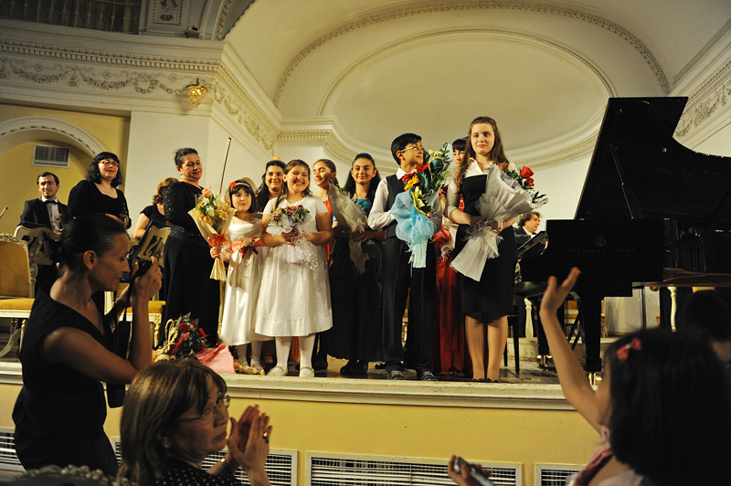 BAKU, AZERBAIJAN.  Children receive flowers and take to the stage for a round of applause from the audience and photographs by doting parents after a classical music performance at the Philharmonic on April 27, 2012.