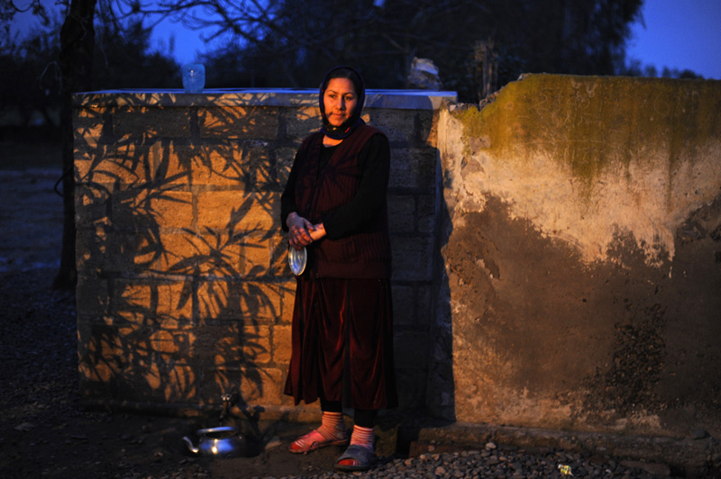 MURGUZALLI, AZERBAIJAN.  Pari Shirmammadova, 46, pours fresh water for tea from a freshwater source on the family's property on November 22, 2011.