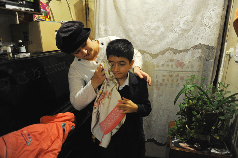 BAKU, AZERBAIJAN.  Gulnar Rzayeva, 35, wipes water from the face of her son, Suleyman Rza, 10, after washing his face before school in one of the last freestanding and undemolished homes on their block despite psychological pressure and the desire of city officials to turn it over to developers for more money on November 1, 2011.  Three families part of one larger extended family live in the home that is completely surrounded by the rubble of the homes of their former neighbors.