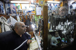 BAKU, AZERBAIJAN.  Haji Fataliyev, a watch repairman known as the best in Baku with a customer in his narrow workspace which is plastered with pictures of the current President of Azerbaijan, Ilham Aliyev, and the current president's father, former president Heydar Aliyev, on November 17, 2011.  (Credit: Amanda Rivkin for Madame Figaro)