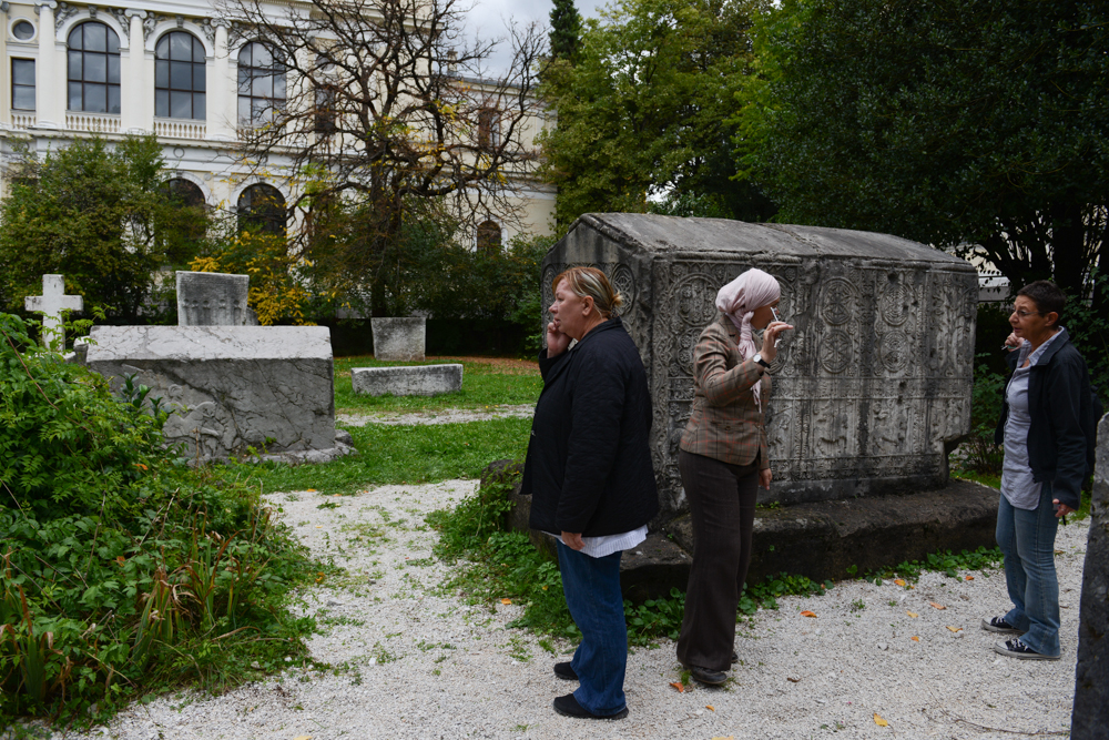 SARAJEVO, BOSNIA AND HERZEGOVINA.  (At right) Andrea Dautovic, 57, a museum adviser and librarian in charge of the exchange of publications, retrieves the key to the ethnographic section of the shuddered Bosnian National Museum from a colleague in the courtyard garden on October 15, 2014.  The museum closed its doors on October 4, 2012 after employees had worked one year without salaries, many of whom continue to work without salaries to this day; the Bosnian National Museum is short the minimum 700,000-800,000 Euro it would need to keep its doors open.