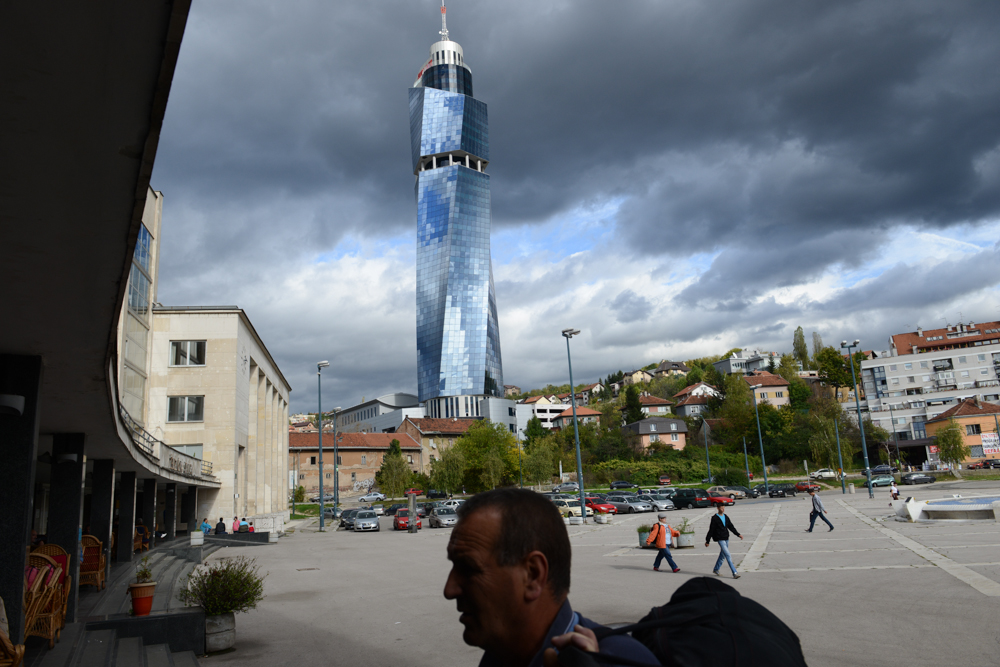 SARAJEVO, BOSNIA AND HERZEGOVINA.  A man carries his bag into the train station, built during the socialist era, and now in the shadow of the Avaz Tower designed by architect Faruk Kapidzic for Bosnian media mogul and former Bosnian nationalist presidential candidate Fahrudin Radoncic on October 17, 2014.