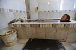 NAFTALAN, AZERBAIJAN.  Quliyev Jeyyub from Tartar, Karabakh in the disputed once Azerbaijani territory now occupied by Armenia, sits in an oil bath at the Sehirli Naftalan Health Center and Hotel on July 19, 2010.  Naftalan is famous for its oil bath treatments across the former Soviet Union and several such treatment centers exist in the town; patients are only allowed to bath for 10 minutes before having oil scraped from their bodies by a nurse attendant and showering.
