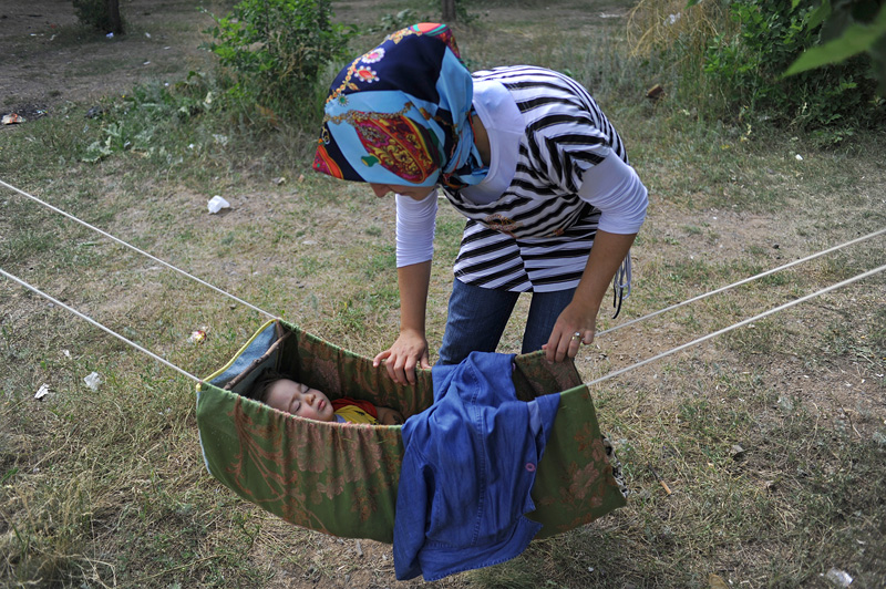 ERZURUM, TURKEY.  A Turkish picnicker rocks her child as he sleeps in a hammock at a site near the Ataturk University in Erzurum, Turkey, the first major city near the route of the Baku-Tbilisi-Ceyhan oil pipeline in Turkey, located just 10 kilometers from the pipeline which traverses numerous villages near the city's airport, on August 8, 2010.