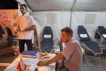 ERZURUM, TURKEY.  A male nurse stands over a man after giving blood at a blood drive organized by the Turkish Red Crescent in a tent on Cumhurriyet Road in Erzurum, Turkey, the first major city near the route of the Baku-Tbilisi-Ceyhan oil pipeline in Turkey, located just 10 kilometers from the pipeline which traverses numerous villages near the city's airport, on August 11, 2010, the first night of Ramadan.  During the month of Ramadan, Muslims are encouraged to give Zakat or money for charity, one of the five pillars of the Muslim faith, and those who cannot are instructed to donate blood and perform other acts of charity.