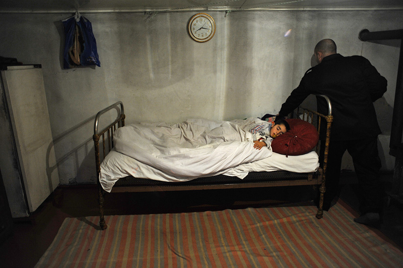 YADILI, AZERBAIJAN.  Maharram Aliyev, 35, pats his son, Emin Aliyev, 3, on the head while he sleeps after returning from his shift as a security guard along the Baku-Tbilisi-Ceyhan (BTC) oil pipeline route in the family's one-room winter home in Yadili, Yevlax Region, Azerbaijan on January 4, 2012.  Aliyev said he earns three to four times the average salary in his village; Aliyev and his father also received compensation funds combined totaling under $3,000 for the disruption to their lands caused by the construction of the BTC pipeline.