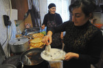 KODA, GEORGIA.  (Left) Venera Arbolishvili, 75, cooks dinner for her extended family with her daughter in the kitchen of her new home in the internally displaced persons (IDP) settlement in Koda, Kvemo Kartli, Georgia on January 20, 2012.  Originally from the village of Eredvi in South Ossetia, formerly a territory of Georgia which was lost to the Russians during the 2008 August War, Arbolishvili said during the war, an unknown assailant fired from a car and killed her husband who died in her arms and subsequently she was forced to flee her home before she could bury him.