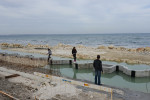 LARNACA, CYPRUS.  People stand on the new break line being used to extend the shoreline out into the sea as it is under construction on March 29, 2013.
