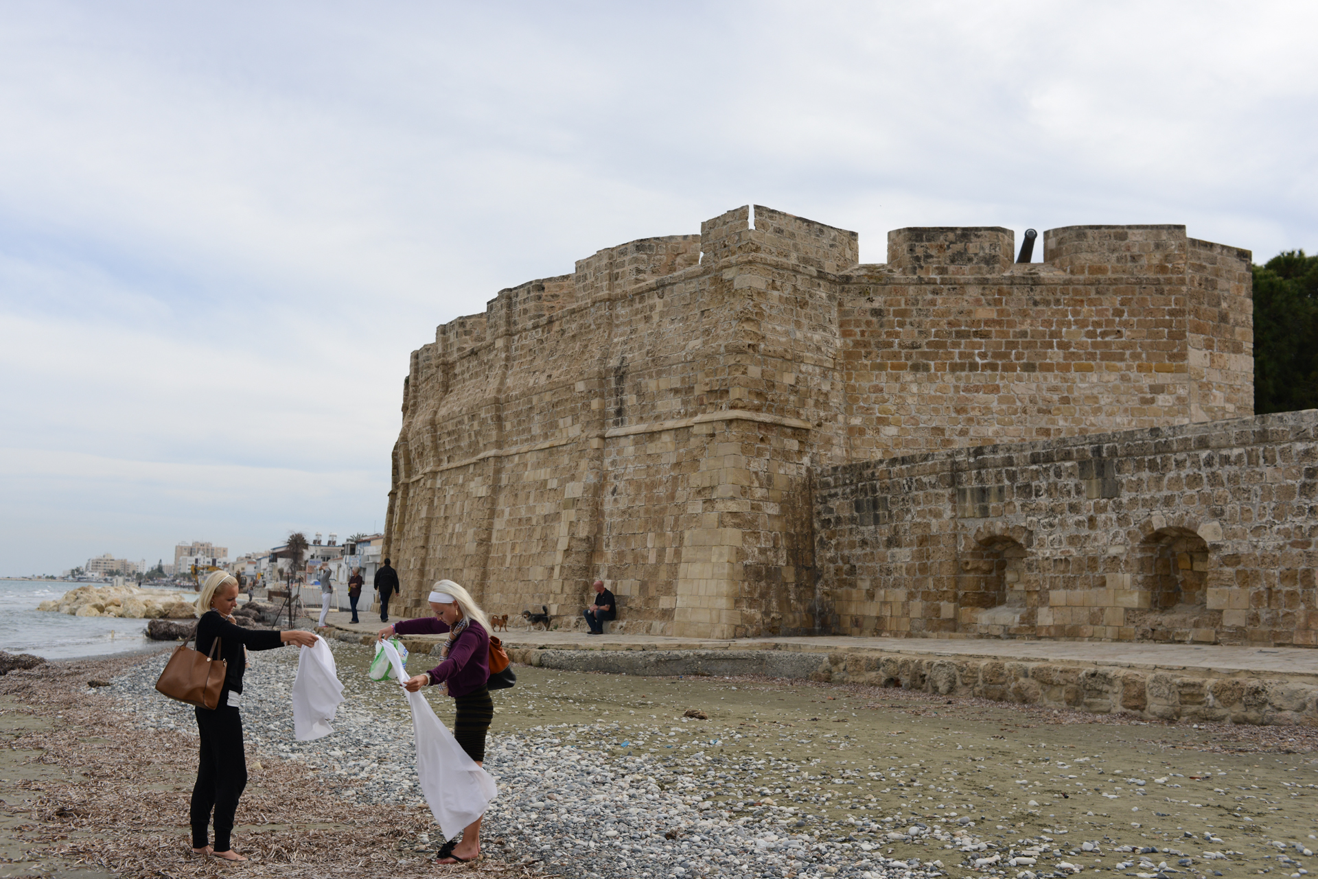 LARNACA, CYPRUS.  Russian women collect their beach blankets beside the Roman fortifications by the seaside on March 29, 2013.