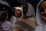 ADDIS ABABA, ETHIOPIA.  Women huddle together under umbrellas amidst throngs of worshippers on St. Teklahaymanot Day at the Teklahaymanot Church on August 30, 2007.