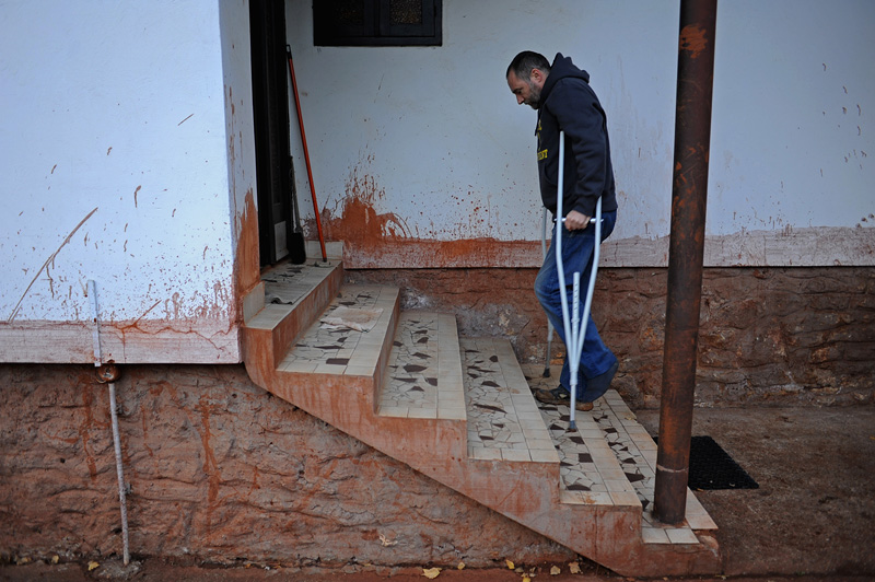 DEVECSER, HUNGARY.  The younger Gyozo Bakonyi enters his parents home in an otherwise abandoned and condemned section of Devecser on November 21, 2010, after an industrial accident sent a torrent of toxic red alumina sludge gushing through Devecser and several nearby villages, killing ten, destroying homes, leaving several families homeless and severely injuring hundreds on October 4, 2010.  Bakonyi survived the accident only to be injured during the clean up the day after; the red marks on the house indicate the height of the sludge at the time of the accident.