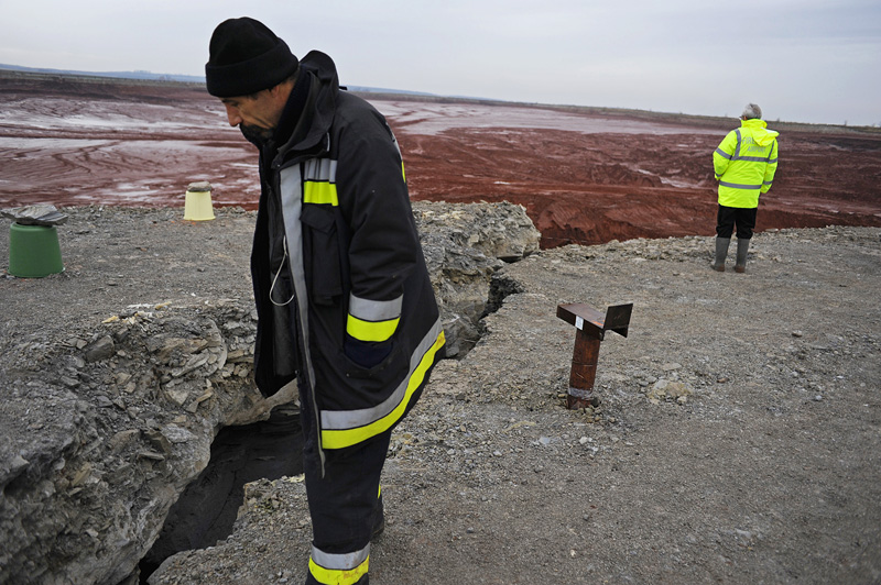 AJKA, HUNGARY.  Disaster management workers inspect the cracks in the wall of the toxic red alumina sludge reservoir at the MAL plant on November 22, 2010, seven weeks after a rupture caused a torrent of the hazardous material to pour into the surrounding countryside and into several villages including Kolontar and Devecser, Hungary, killing ten, including a 14 month old baby, injuring hundreds and leaving several families homeless.