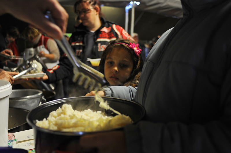 DEVECSER, HUNGARY.  A young girl looks on as volunteers serve free lunch to residents of Devecser in a makeshift soup kitchen in a Hungarian military tent pitched beside the Geza Gardonyi Primary School on November 24, 2010, many of whom were left homeless and bereft of the only home they had and knew due to an industrial accident at the MAL plant in nearby Ajka, Hungary that sent a torrent of toxic red alumina sludge gushing through the village and several surrounding villages, injuring hundreds, leaving several families homeless and killing ten.