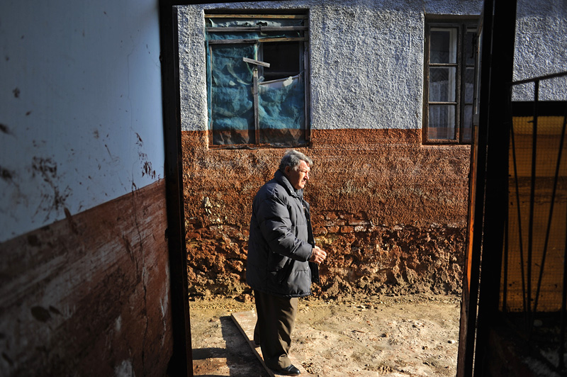 DEVECSER, HUNGARY.  Geza Csenki, 63, outside the entrance of his ruined and uninhabitable home on November 25, 2010, less than seven weeks after an industrial accident at the MAL plant in nearby Ajka, Hungary sent a torrent of toxic red alumina sludge gushing through Devecser and several surrounding villages, killing ten, injuring hundreds and leaving several families homeless.  Csenki's efforts to organize demonstrations on behalf of the survivors have been met with an extraordinary response by the authorities who have gone to great lengths to accommodate Csenki and the complaints he has brought forward on behalf of villagers in an effort to avoid official embarrassment.