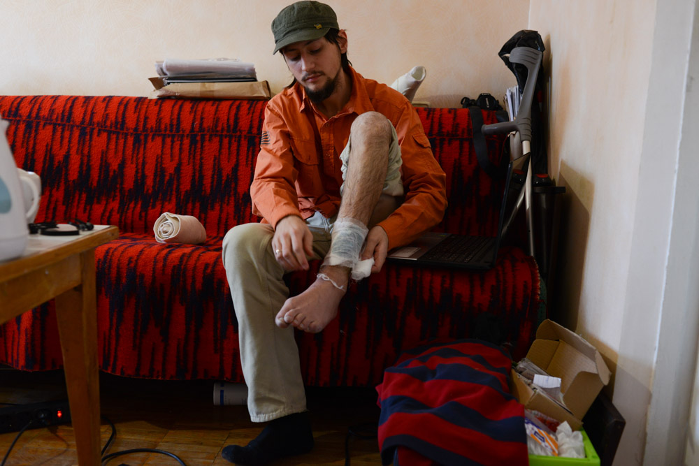 MYKOLA, 24Mykola, 24, from Kiev sits in his apartment in a Soviet-style flat near the outskirts of Kiev, Ukraine on April 4, 2014.  Mykola was shot in the left leg near his ankle at 4:30am on February 19, 2014, while filming and walking up steps in the middle of Maidan Square.{quote}They aimed at journalists and those with cameras to start clearing Maidan.  I personally don't know who did this.  But I know it was these special Alpha troops led by Asaveluk and I know he has not been relieved of his duty.  I was there from the very first day, the night November 21st.  We were aiming to change the rules of the game.  What I see now is a change of power and authorities without changes to the system.  If the change will not come, we will have a third Maidan and it will be more serious.{quote} -Mykola