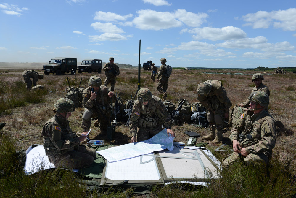 DRAWSKO POMORSKIE TRAINING AREA, POLAND.  American soldiers with the Fourth of the 319th Airborne Field Artillery Regiment of the 173rd Airborne Brigade Combat Team examine their maps and communications following an airdrop from a C-17 aircraft that took off from Nuremberg, Germany and dropped on June 15, 2015.  NATO is engaged in a multilateral training exercise {quote}Saber Strike,{quote} the first time Poland has hosted such war games, involving the militaries of Canada, Denmark, Germany, Poland, and the United States.