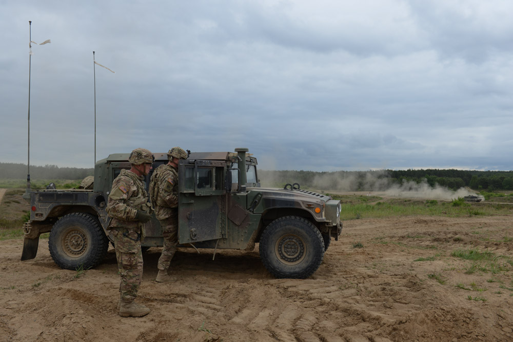 DRAWSKO POMORSKIE TRAINING AREA, POLAND.  American soldiers with the 2nd Battalion, 7th Infantry Regiment, 1st Armored Brigade Combat Team, 3rd Infantry Division based out of Fort Stewart, Georgia beside a Humvee before a live fire exercise with a German-made Danish Leopard 2A5 tank on the horizon on June 16, 2015.  NATO is engaged in a multilateral training exercise {quote}Saber Strike,{quote} the first time Poland has hosted such war games, involving the militaries of Canada, Denmark, Germany, Poland, and the United States.