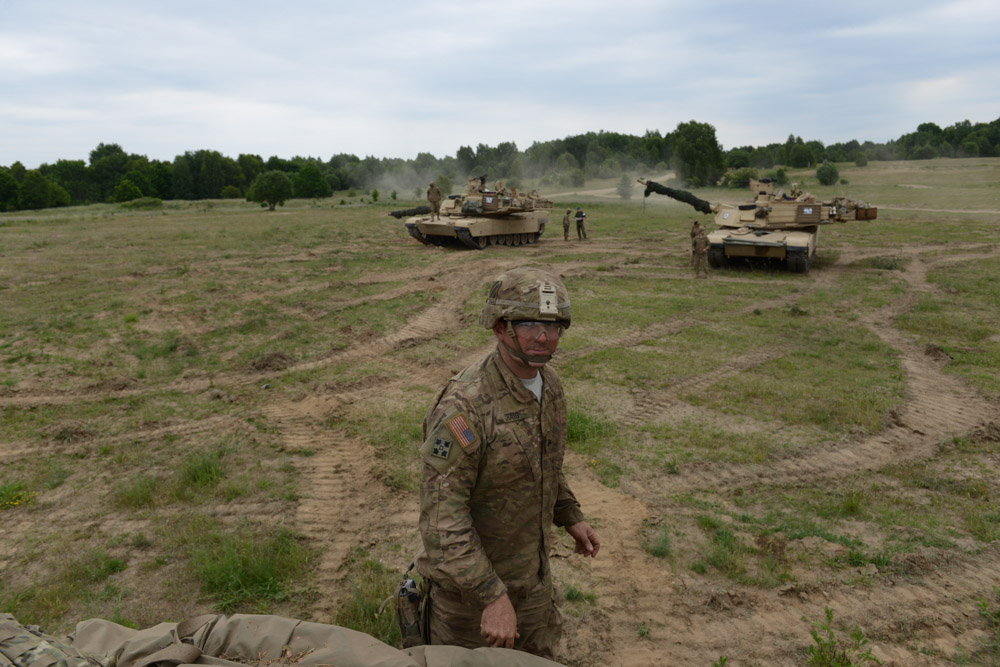 DRAWSKO POMORSKIE TRAINING AREA, POLAND.  American soldiers with Delta Company, 2nd Battalion, 7th Infantry Regiment, 1st Armored Brigade Combat Team, 3rd Infantry Division with M1A2 Abrams tanks after a tank training exercise practicing infiltration on June 12, 2015.  NATO is engaged in a multilateral training exercise {quote}Saber Strike,{quote} the first time Poland has hosted such war games, involving the militaries of Canada, Denmark, Germany, Poland, and the United States.