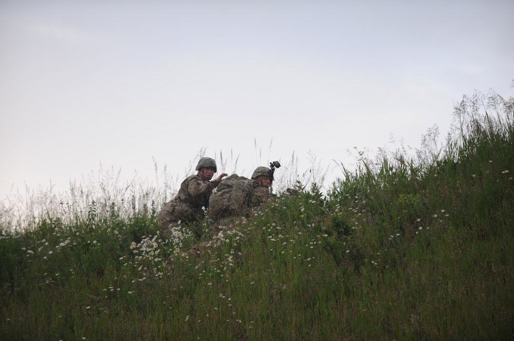 SWIDWIN AIRFIELD, POLAND.  American soldiers with the 1st Battalion, 503rd Infantry Regiment, 173rd Airborne Brigade maintain their position on a grassy knoll after parachuting in from a C-130 during an airfield seizure exercise on June 16, 2015.  NATO is engaged in a multilateral training exercise {quote}Saber Strike,{quote} the first time Poland has hosted such war games, involving the militaries of Canada, Denmark, Germany, Poland, and the United States.