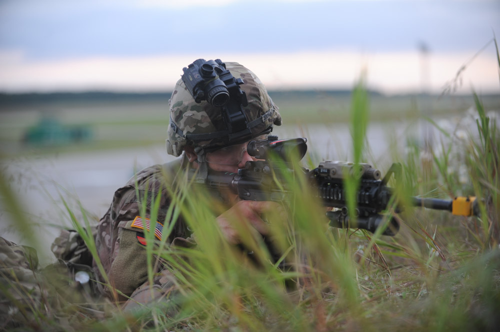 SWIDWIN AIRFIELD, POLAND.  PB2 Michael Simkin with the 1st Battalion, 503rd Infantry Regiment, 173rd Airborne Brigade maintains his position on a grassy knoll after parachuting in from a C-130 during an airfield seizure exercise on June 16, 2015.  NATO is engaged in a multilateral training exercise {quote}Saber Strike,{quote} the first time Poland has hosted such war games, involving the militaries of Canada, Denmark, Germany, Poland, and the United States.